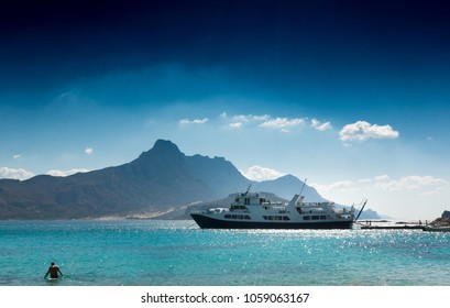 Scenic view of sea, cruise ship and mountain against cloudy sky, Crete island, Greece