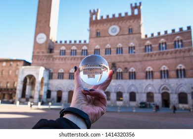 Scenic view of Siena cityscape: hand holding a lens ball in front of Campo Square (Piazza del Campo) and town hall building (Palazzo Comunale).  Italy