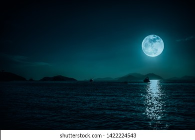 Scenic view of small boat in calm sea water at night time and super moon. serenity nature background, outdoor at night time. The moon taken with my own camera.