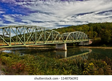 A scenic view of a small steel bridge in rural Elk County Pennsylvania. With a beautiful reflection in the water below
