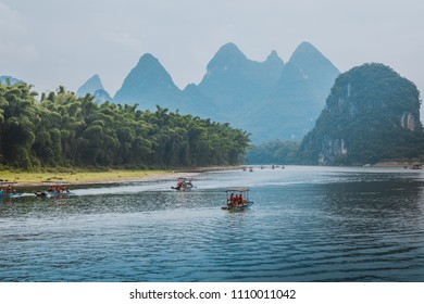 Scenic view of small tourist bamboo rafts sailing along the Li River among green woods and karst mountains at Yangshuo County of Guilin, China. Yangshuo is a popular tourist destination of Asia.