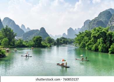 Scenic view of small tourist bamboo rafts sailing along the Yulong River among green woods and karst mountains at Yangshuo County of Guilin, China. Yangshuo is a popular tourist destination of Asia.