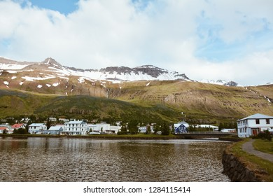 Scenic view of small town Seydisfjordur on East Iceland in summer with lake and snow in the mountains - vintage film look