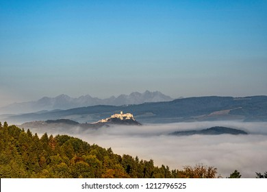 Scenic view of Spis Castle in front of majestic High Tatras mountain range surrounded with morning fog/mist in autumn time.