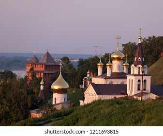 Scenic view at St. Elijah's Church, domes of Church of St. John the Baptist and guard towers of of Nizhny Novgorod Kremlin with Volga river in the background at sunset