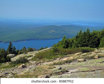 Scenic view from the summit of Cadillac Mountain in Acadia National Park in Maine, with pink granite boulders, lichen and low shrubbery, and glistening water below.