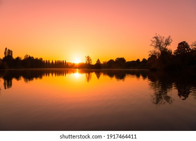 A scenic view of the sun reflecting on a calm sea during a beautiful sunset