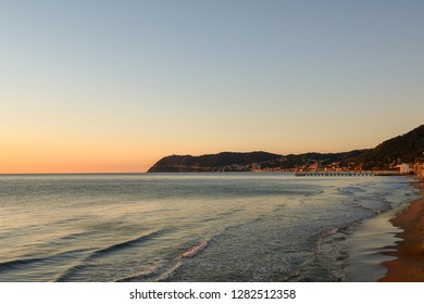 Scenic view at sunrise of the Ligurian coast from the sandy beach of Alassio with Laigueglia and Capo Mele in the background, Liguria, Italy