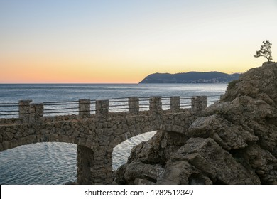 Scenic view at sunset of the Ligurian Sea from the cliff of Punta Santa Croce with Capo Mele on the horizon, Alassio, Liguria, Italy