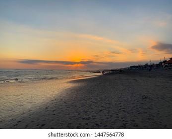 Scenic view of the sunset on the surf beach Batu Bolong in Canggu on Bali island, Indian ocean coast and beautiful Bali sunset