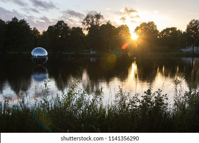 Scenic view of the swedish lake Trummen in Vaxjo with a disco ball on the lake, in the region Smaland, Sweden on a sunny day with some clouds on the sky and reflection in the evening sunset.