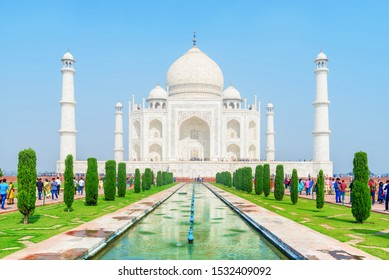 Scenic view of the Taj Mahal on blue sky background in Agra, India. The white marble mausoleum reflected in artificial pool. The Taj Mahal is a popular tourist attraction of South Asia.