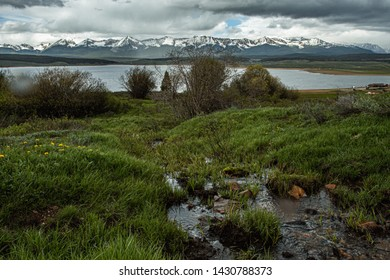 A scenic view of Taylor Reservoir with a stream in the foreground and mountains in the distance.