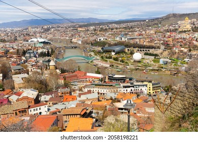 Scenic view of Tbilisi Old town on banks of Kura river on sunny spring day overlooking modern pedestrian Bridge of Peace, Music Theater building and air balloon in Rike Park, Georgia