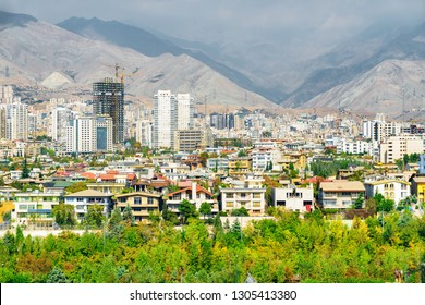 Scenic view of Tehran, Iran. Mountains are visible in background. Colorful residential buildings among green trees. Cityscape on sunny day. Tehran is a popular tourist destination of the Middle East.
