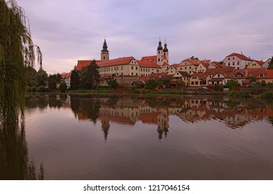 Scenic view of Telc castle, lake, Name of Jesus Church and tower of the Church of St. Jakub. Buildings are reflected in the water. Early morning landscape. A UNESCO World Heritage Site.