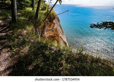 """Scenic view through trees towards the chalk cliffs of Rügen and the Baltic coast (""""Steilküste"""") seen from Hochuferweg hiking path, Jasmund National Park, Rügen, Mecklenburg-Vorpommern, Germany."""