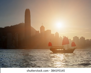 Scenic view of traditional Chinese wooden sailing ship with red sails in Victoria harbor at sunset. Tourist sailboat and Hong Kong Island skyline. Silhouettes of skyscrapers are visible in background.