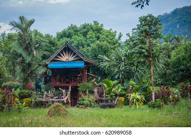 Scenic view of a traditional multicolored wooden house of local people on a meadow of the rain forest of Khao Sok sanctuary, Thailand