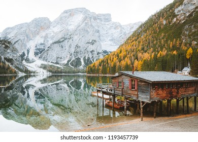 Scenic view of traditional wooden boathouse at famous Lago di Braies with Dolomites mountain peaks reflecting in lake, South Tyrol, Italy mountain peaks reflecting in lake, South Tyrol, Italy