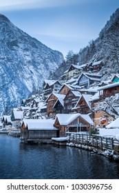Scenic view of traditional wooden houses in famous Hallstatt lakeside town in the Alps in mystic twilight during blue hour at dawn on a beautiful cold day in winter, Salzkammergut region, Austria