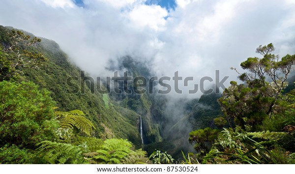 Scenic view of Trou de fer waterfall on Reunion Island National Park with cloudscape background and jungle in foreground.
