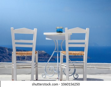Scenic view with two wooden chairs, a small table and a breathtaking sea view in Santorini island, Greece. Amazing view of the Aegean sea, Cyclades, Greece, Europe.