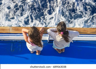 Scenic view of two young children staring at the deep blue sea of aegean in Greece