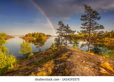 Scenic view of uninhabited islands. Epic sky. Colored rainbow. Sunny clear day on the water. Yellow moss covers the rocks. Magical northern nature. National park. Ladoga lake. Republic of Karelia