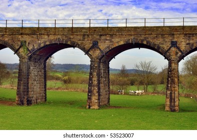 Scenic view of Victorian railway viaduct in English countryside.