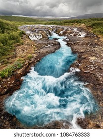 Scenic view of a waterfall with blue coloring, in the background a mountain range - Location: Iceland, Golden circle