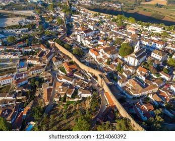 Scenic view of white houses red tiled roofs, and castle from wall of fortress. Obidos village, Portugal.