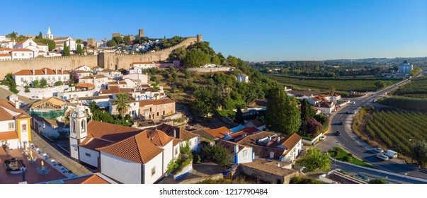 Scenic view of white houses red tiled roofs, and vineyard castle from wall of fortress. Obidos village, Portugal.