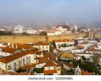 Scenic view of white houses red tiled roofs, and castle from wall of fortress with clouds. Obidos village, Portugal.