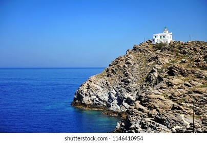 Scenic view of white lighthouse on cliffs by sea. Beautiful natural seascape, Paros island, Greece