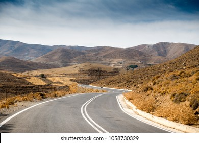 Scenic view of winding road leading to mountain, Crete, Greece