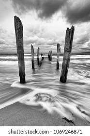 Scenic view of wooden poles on a beach, the movement of the waves is shown in addition to a colorful evening sky, black and white version - Location: Baltic Sea, Rügen Island