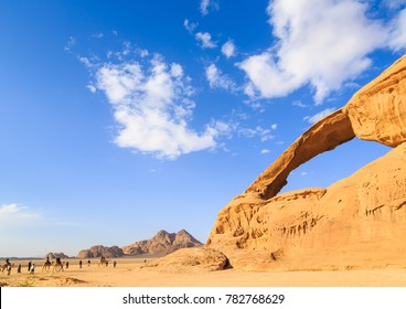 Scenic view of the yellow colored arch rock in the Wadi rum desert in Jordan witha group of persons on camels walking through at daytime