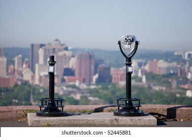A scenic viewer binoculars looking out a urban scene