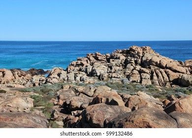 Scenic views of  the rocky landscape at Sugar Loaf Rock South Western Australia in the blue Indian Ocean  a popular fishing and hiking destination with its treeless green  dunes and  splashing waves .