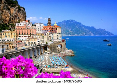 Scenic village along the Amalfi Coast of Italy. View of Atrani with flowers against the blue sea during summer.