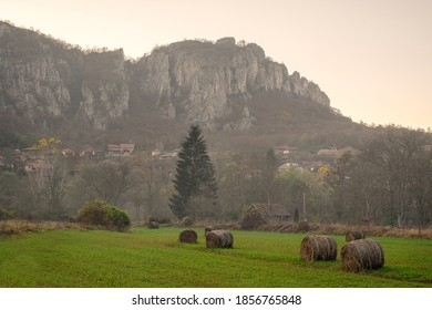 Scenic village Vlasi in Jerma river canyon, at the base of massive, rocky cliff and foreground hay bales on a green field - Shutterstock ID 1856765848