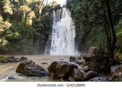 Scenic waterfal hidden in vietnamese jungle with big stones in front