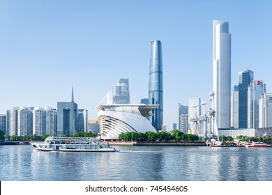 Scenic white tourist boat sailing along the Pearl River in Guangzhou, China. Wonderful view of skyscrapers and other modern buildings at the Zhujiang New Town. Guangzhou skyline. Summer cityscape.