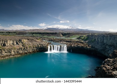 Scenic wide angle view of Thjofafoss waterfall and Hekla mountain on the background covered by snow