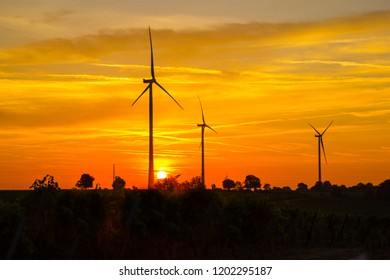 Scenic wind turbines in the morning at sunrise with beautiful dramatic sky behind them. Concept of sustainability.
