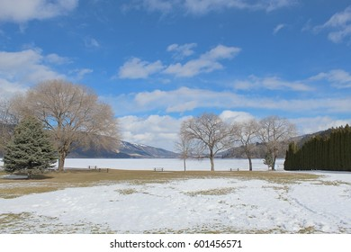 Scenic winter ice covered lake landscape with snow covered grass field in foreground.  Tall trees and hedges on shoreline. Mountains, white clouds and bright blue sky in background.