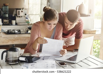 Scenic young family doing paperwork at home. Wife looking worried sitting at kitchen table with lot of paper documents, laptop, calculator and cell phone, studying bill together with her husband