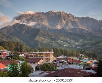 A scenicview of a rocky mountain range of Kinabalu with a dwelling and green vegetation in the foreground, Malaysia