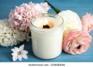 Scented candle with burning wooden wick and flowers on blue table, closeup